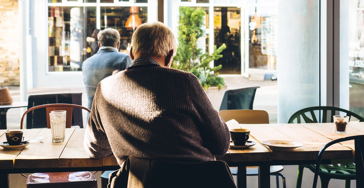 man sitting at a cafe table